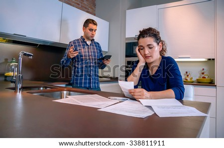 Desperate young couple with many debts reviewing their bills. Financial family problems concept. - stock photo