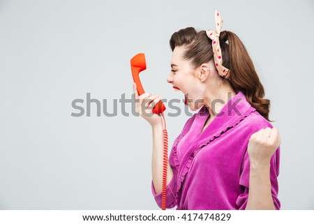 Desperate young housewife holding red telephone receiver and shouting - stock photo