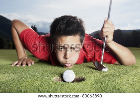 Desperate young male golf player in red shirt and putter lying on golf green and blowing golf ball into cup, focus on ball. - stock photo
