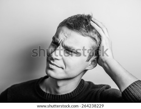 Desperate young man covering with his head in his hands - stock photo