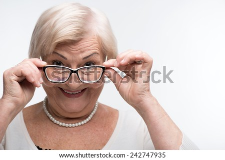 Desperately curious. Closeup portrait of a beautiful senior woman adjusting glasses and smiling at you standing near copy space over white background - stock photo