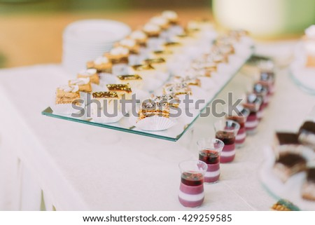 Dessert buffet with delicious sweet chocolate icing bakery on snow-white tablecloth. Close-up - stock photo