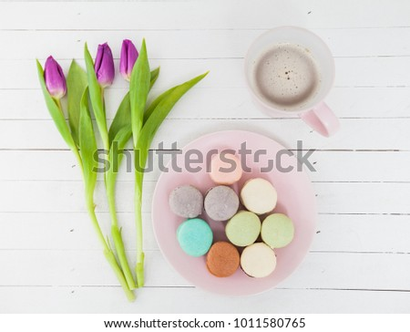 Dessert Coffee Flowers , almond cookies macarons colorful dessert and tulip over rustic white background