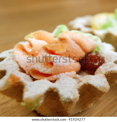 dessert colorful baskets cream sprinkled powdered sugar standing table closeup - stock photo