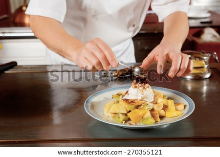 Dessert cooking. Close-up of hands of cook putting cream, jam and strawberry on a fruit dessert