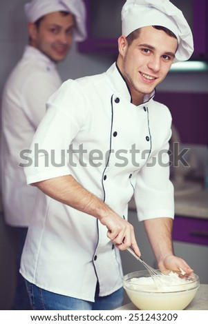 Dessert cooking concept. Portrait of a smiling male chef with his coworker cooking food and standing in the modern kitchen of restaurant. Indoor shot - stock photo