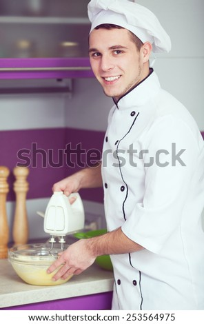 Dessert cooking concept. Portrait of smiling male chef cooking food and standing in the modern kitchen of restaurant. Indoor shot - stock photo