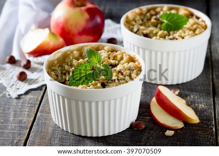 Dessert crumble with apple and nuts on a dark wooden table - stock photo