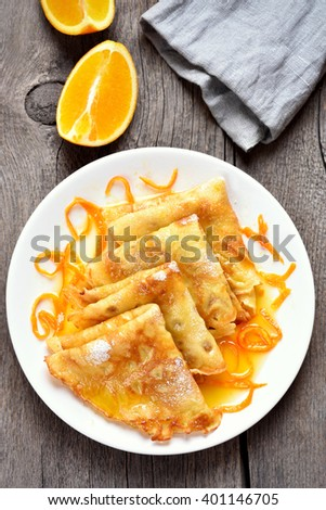 Dessert delicious crepes with orange syrup on wooden background, top view - stock photo