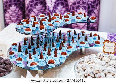 Dessert for holiday. Dark chocolate truffles sprinkled with cocoa, zephyr in chocolate, candy with chocolate and sweetness. Wedding dessert. - stock photo