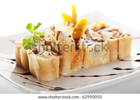 Dessert Maki Sushi - Roll with Various Fruit and Cream Cheese inside. Pancake outside. Served with Chocolate Sauce - stock photo