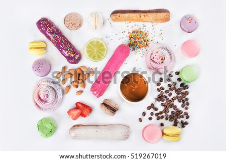 Dessert mix of color macaroons, and sweets eclairs, coffee on white background. top view.