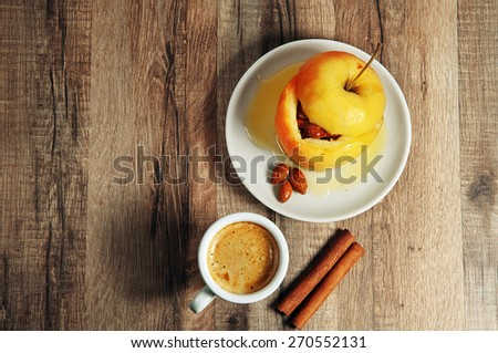 Dessert of baked apples stuffed with nuts and drizzled with honey. dessert apple standing on a wooden table. Next to the dessert of apple, a cup of fresh, organic coffee and two cinnamon sticks - stock photo