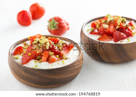 dessert of yogurt with fresh strawberries and pistachios in bowls, close-up - stock photo