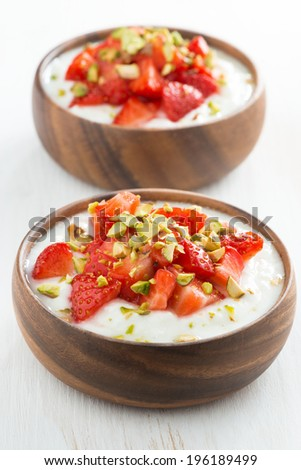 dessert of yogurt with fresh strawberries and pistachios in wooden bowls, close-up, vertical, top view - stock photo