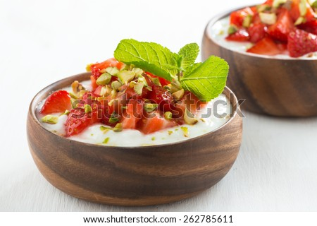 dessert of yogurt with fresh strawberries, pistachios and mint, close-up - stock photo