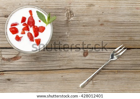 Dessert. Strawberry with cream and mint on a wooden background, close up, top view - stock photo