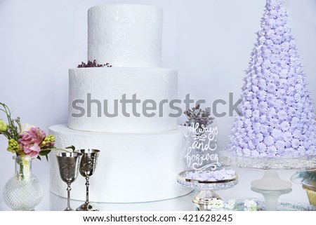 Dessert table classic white wedding cake. Image of a beautiful wedding cake at wedding reception bouquets on table. decor lavende rmeringue - stock photo