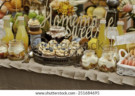Dessert table for a party. gugelhupf with bilberries, fig and cream, cupcakes, sweetness and flowers - stock photo