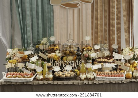 Dessert table for a party. gugelhupf with bilberries, fig and cream, cupcakes, sweetness and flowers