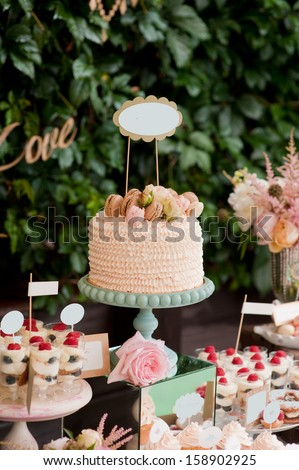 Dessert table for a party. Ombre cake, sweets and flowers