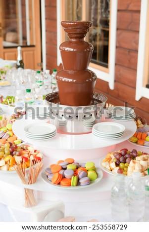 Dessert table with chocolate machine fountain - stock photo