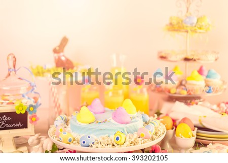 Dessert table with Easter cake decorated with traditional Easter marshmallow chicks. - stock photo