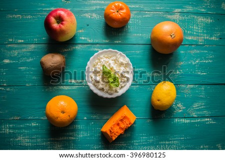 Dessert with cottage cheese and ripe fresh fruit on wooden turquoise background. top view - stock photo