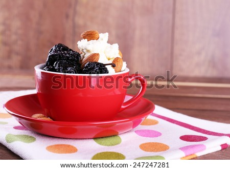 Dessert with prunes and almonds in red cup on napkin and wooden planks background - stock photo