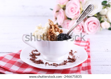 Dessert with prunes in cup with bouquet of roses on color wooden table background - stock photo