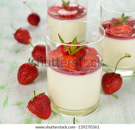Dessert with strawberries in a glass on a white  table