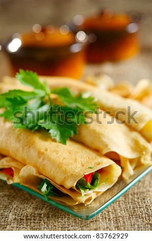 Dessert with the rolled pancakes in a glass plate on the background of two brown pots and canvas cloth - stock photo