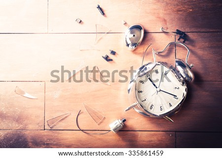 destroyed alarm clock on a wooden background - stock photo