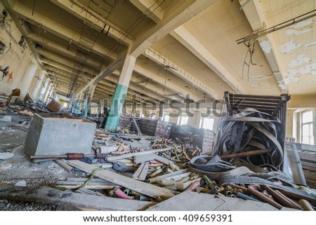 Destroyed interior of factory hall with great mass contains money things around. Creative compose photography by using wide angle lens. - stock photo