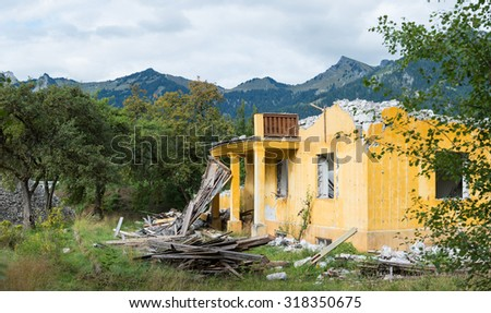destroyed old orange house next to trees and mountains - stock photo