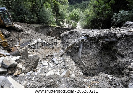 Destroyed road landslide damaged in powerful flood. Collapsed road on the mountain - stock photo