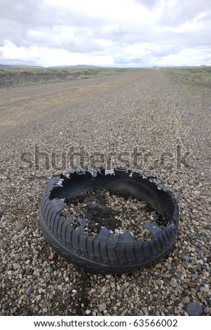 Destroyed rubber tire on gravel road, Iceland - stock photo