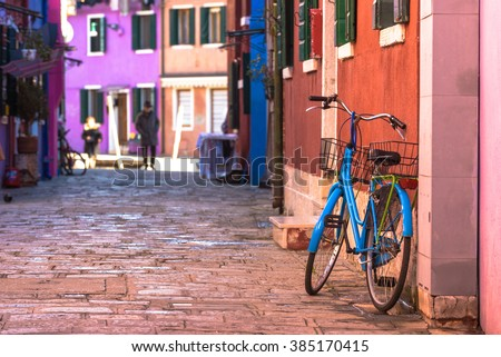Destroyed sometimes bicycle leaning colored house in Burano, Italy. - stock photo