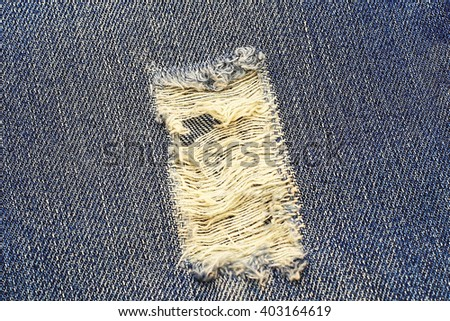 Destroyed torn blue denim jeans background, close up - stock photo