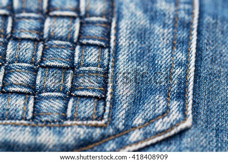 Destroyed torn blue jeans wicker patch, close up, shallow dof - stock photo