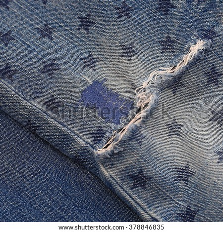 Destroyed torn denim blue jeans with patch and star print, close up  - stock photo
