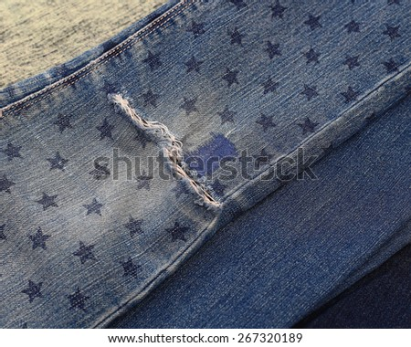 Destroyed torn denim blue jeans with patch and star stamp - stock photo