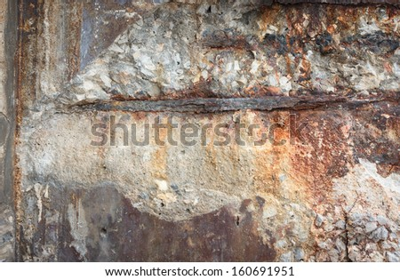Destruction of a concrete wall with rusty