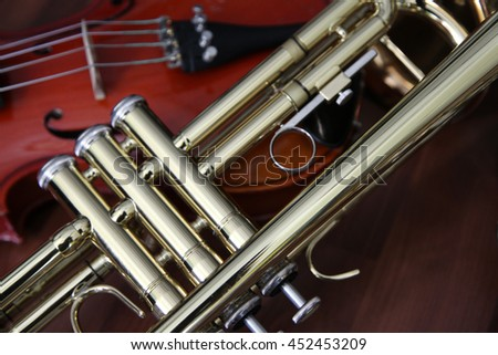 Detail close up of a trumpet and violin still life on a wood surface - stock photo