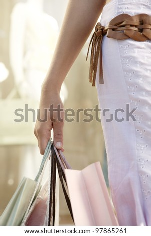 Detail close up of a woman's hand holding shopping bags by fashion store.