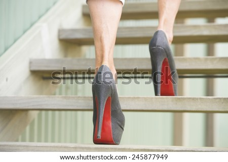 Detail close up of woman in high heel stiletto shoes walking up wooden stairs with blurred background. - stock photo