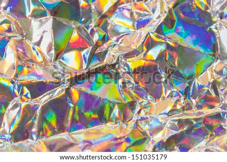 Detail close up of wrinkled metallic paper as a colorful fantasy background image in soft colors with focus at the center - stock photo