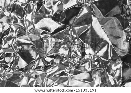 Detail close up of wrinkled metallic paper as a monochrome structured background image in black and white with focus at the center - stock photo