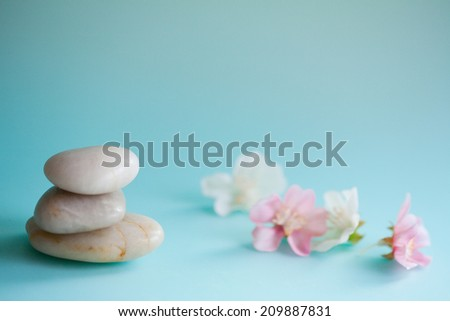 Detail close up still life view of a pile of natural smooth white stones balancing in a stack against pink blossom flowers in a blue health spa background Nature objects and zen energy. - stock photo