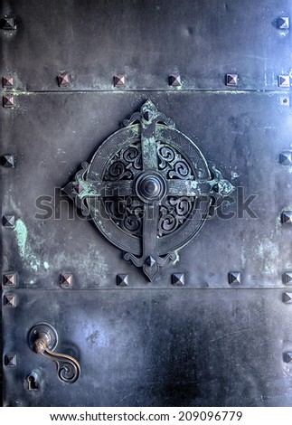 Detail from a metal door. Slightly noisy.  - stock photo